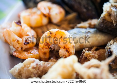 Plate with cooked mussels, shrimps, squid and fish