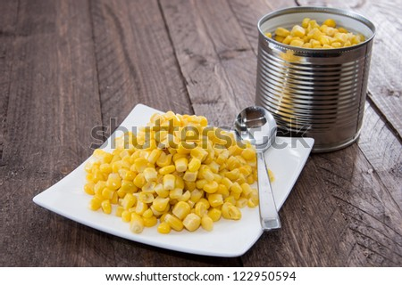 Plate with Corn on wooden background - stock photo