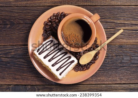 Plate with cup of hot coffee and creamy cake on dark wooden table, top view - stock photo