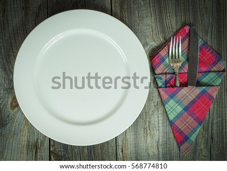 plate with cutlery on a gray wooden table, vintage toning