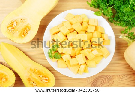 Plate with diced butternut squash and butternut squashes on a wooden background. - stock photo