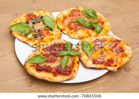 plate with different kinds of small pizzas on a wooden table