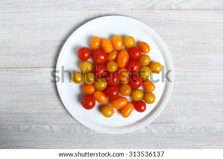 Plate with different tomato cultivars on plank wooden table. Directly above.
