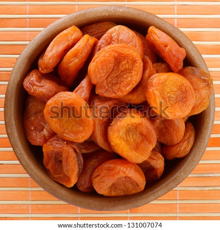 Plate with dried figs, on orange tablecloth. - stock photo