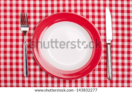 Plate with fork and knife on a red and white checked table cloth