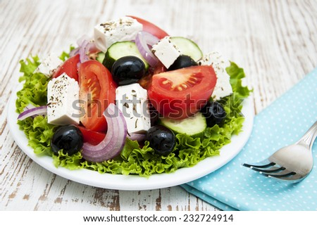 Plate with Fresh Greek salad on a wooden background
