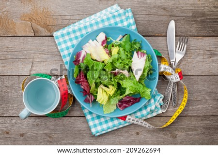 Plate with fresh salad, measure tape, cup, knife and fork. Diet food on wooden table - stock photo