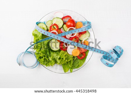 Plate with fresh vegetables salad and measured tape isolated on white - stock photo