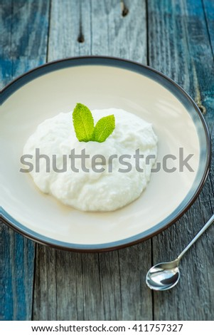 Plate with fresh yogurt on rustic wooden table