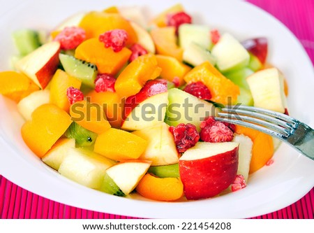 Plate with fruit salad on table - stock photo