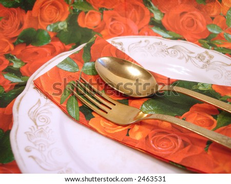 plate with golden fork and spoon on floral serviette - stock photo