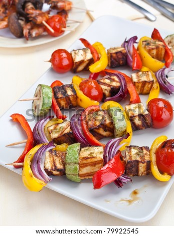plate with halloumi and vegetables kebabs on a table - stock photo