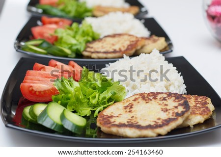 Plate with homemade tasty vegan meal from salad, tomatoes, cucumber and healthy vegetable  cutlets - stock photo