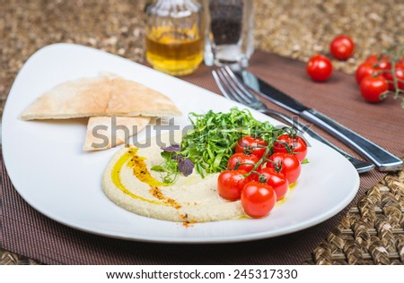 Plate with hummus dip and pita bread, a common tapas or starter dish in middle eastern cuisine - stock photo