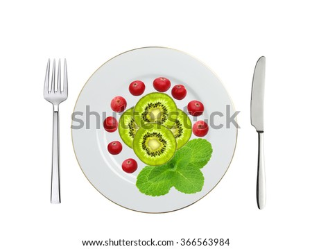 plate with kiwi slices, cranberry and mint herb, knife and fork isolated on white - stock photo