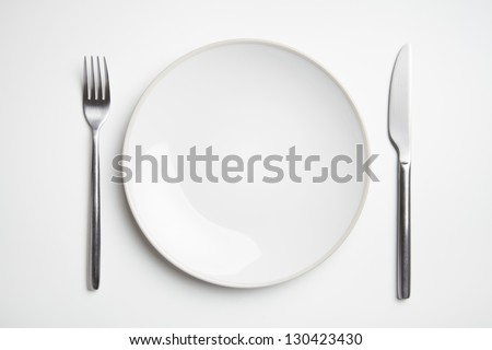Plate with knife and fork on white table top - stock photo