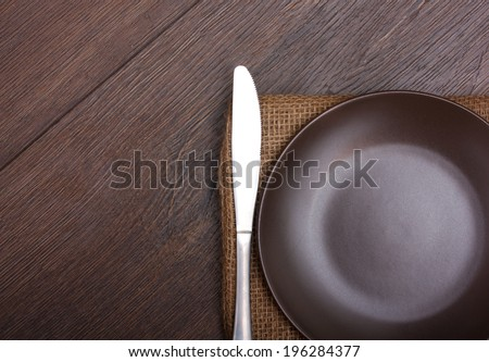 Plate with knife on wooden background
