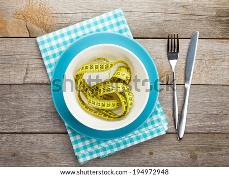 Plate with measure tape, knife and fork. Diet food on wooden table - stock photo
