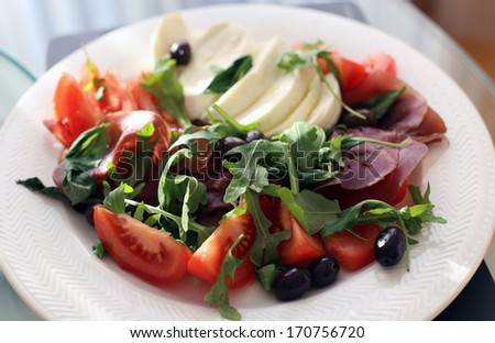 Plate with mozarella, bresaola, tomatoes, rucola and olives