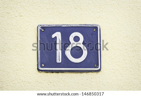 Plate with number eighteen, detail of an old metal plate with information and numbers