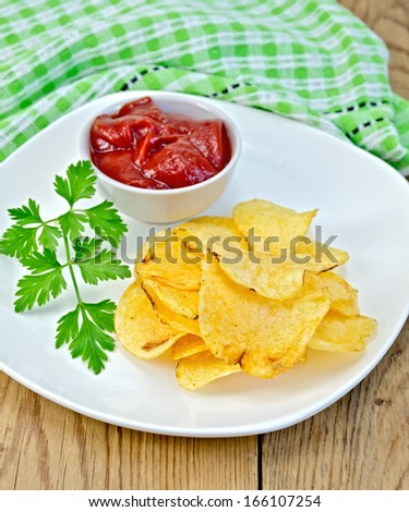 Plate with potato chips, a bowl with tomato ketchup, green cloth on a background of wooden boards