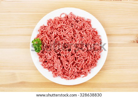 Plate with raw ground beef on wood - stock photo