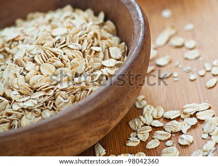 Plate with raw oatmeal on wooden table. - stock photo
