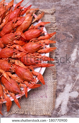 Plate with red boiled crawfish on a wooden table in rustic style, selective focus - stock photo