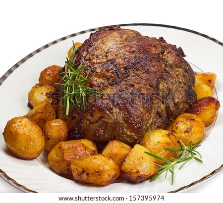 Plate with roast leg of lamb, potatoes and rosemary on white background - stock photo