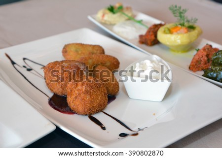 Plate with roasted cheese balls and sauce in front of another dish with cooked vegetables in restaurant - stock photo