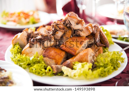 Plate with roasted chicken on holiday table - stock photo