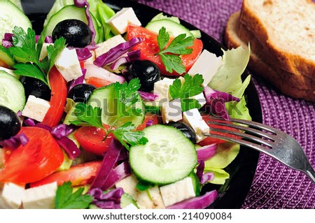Plate with salad on purple table - stock photo