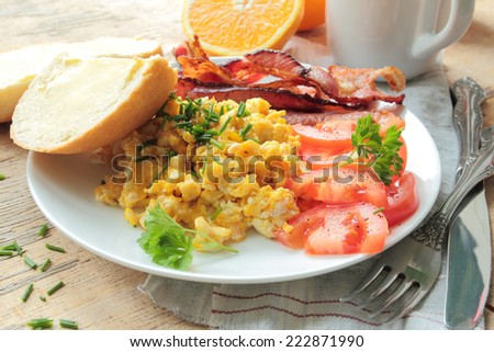 Plate with scrambled eggs, bacon and tomatoes - stock photo