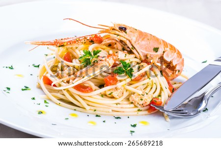 Plate with seafood spaghetti, pasta.Italian restaurant menu plate, noodles with prawns, langoustines, lobster.Italian food background. - stock photo