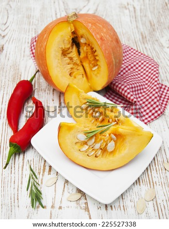 Plate with sliced pumpkins on kitchen table - stock photo