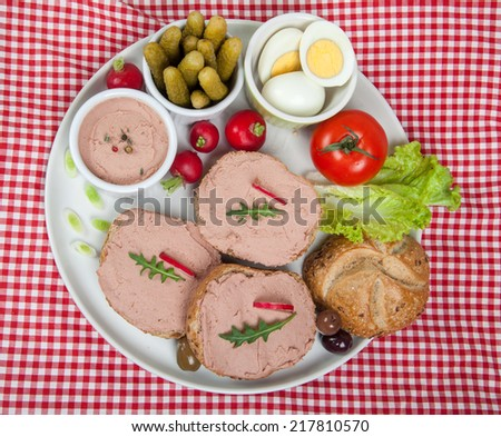 plate with slices of bread with home made pate, vegetables and eggs - stock photo