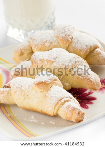 Plate with small homemade croissants and milk glass. Shallow dof. - stock photo