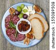 Plate with snacks, sausage, cheese, nuts and fruit, top view - stock photo