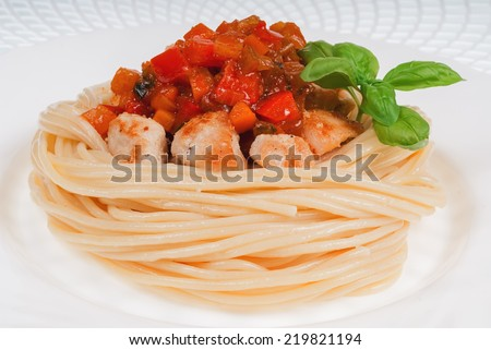 Plate with spaghetti, sauce and basil on white background. Chicken in sweet and sour sauce with pineapple and pasta. - stock photo