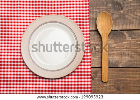 Plate with spoon on wooden table with red checked tablecloth