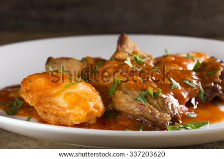 Plate with stew of pork meat (goulash) and dumplings - stock photo
