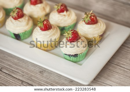 plate with strawberry topped cupcakes on wooden table - stock photo