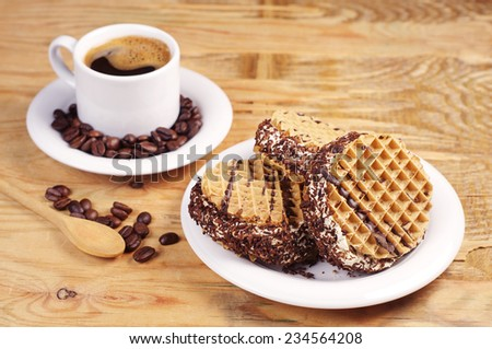 Plate with sweet chocolate cake and cup of hot coffee on old wooden table