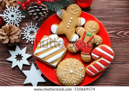 Plate with tasty cookies and Christmas decor on wooden table