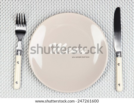 "Plate with text ""Menu"", fork and knife on tablecloth background"
