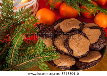 Plate with the traditional brownie cookies, covered with peanut butter, on Christmas table with mandarin oranges and fir branches.