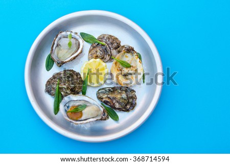 Plate with tree preparations of oysters, on a blue background - stock photo