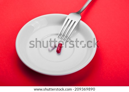 Plate with two pills and a fork on a red table