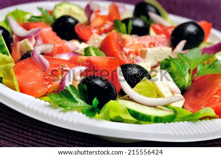 Plate with vegetable salad on table