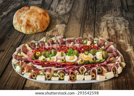 Plateful of Serbian Meze with domestic Pita Bread loaf, placed on very old, weathered, cracked, scratched, peeled off, Wooden Table. - stock photo